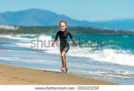 laughing cute little girl jumping in a wetsuit on the beach