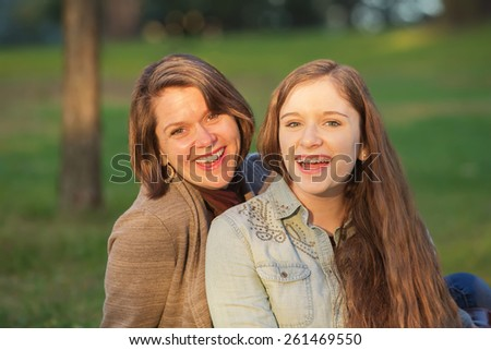 Laughing cute mother and female teenager sitting together - stock photo