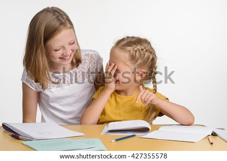 Laughing cuties during the process of doing homework. Two sisters with positive emotions of happiness and fun. Children do not want to study.