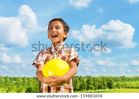 Laughing dark boy holding yellow volley ball standing in the park on sunny day with blue clouds on background - stock photo
