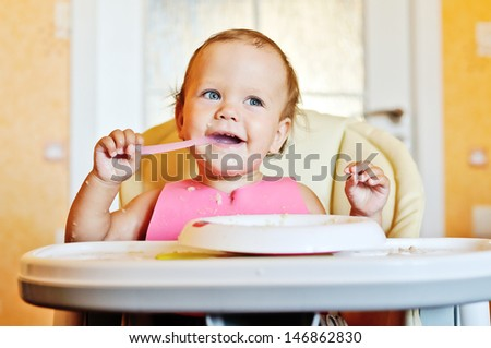 laughing eating baby girl with dirty face - stock photo