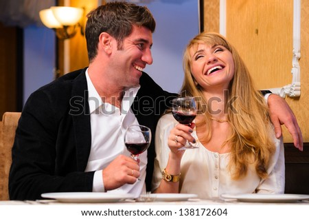laughing embracing couple is sitting at restaurant and drinking wine - stock photo
