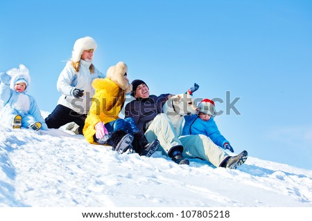 Laughing family and Labrador Retriever dog in winter park - stock photo