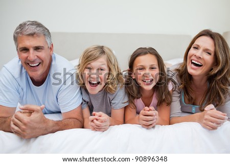 Laughing family lying on the bed together