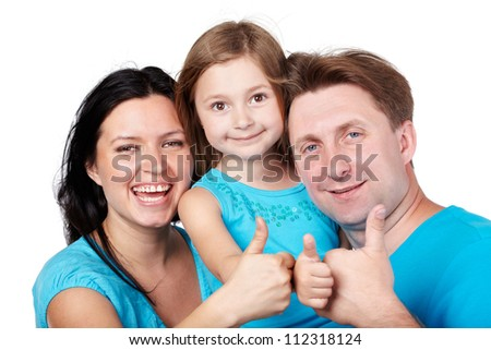 Laughing family of three in blue shirts gives their thumbs up. - stock photo