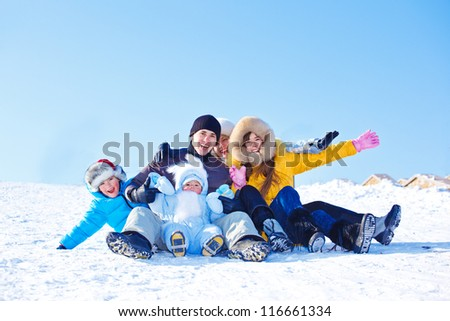 Laughing family on a snowy hill