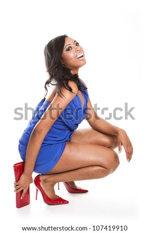 Laughing fashionable African woman in a short blue dress with red stilettoes and matching purse crouching down on the floor isolated on white - stock photo