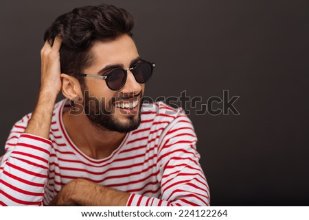 Laughing fashionable young man in sunglasses - stock photo