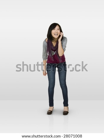Laughing female teen talking on mobile phone - stock photo