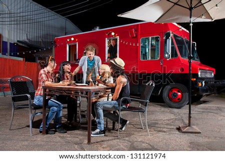 Laughing friends at food truck eating pizza slices - stock photo