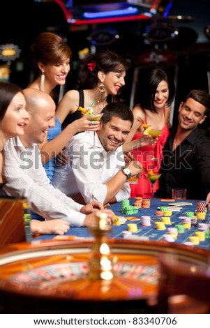 laughing friends enjoying a gambling night - stock photo