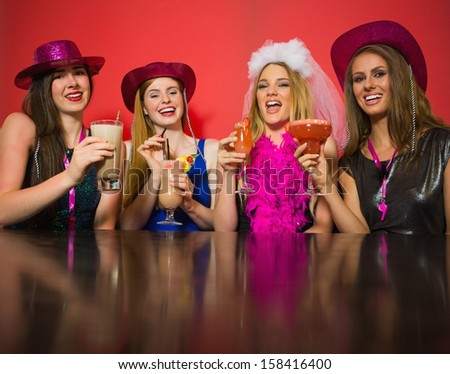 Laughing friends having hen party holding cocktails looking at camera - stock photo