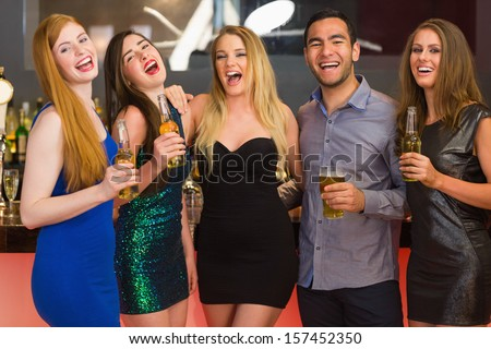 Laughing friends holding beers posing and looking at camera in the nightclub - stock photo
