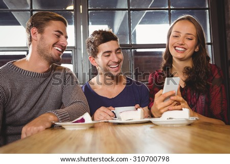 Laughing friends looking at smartphone at coffee shop - stock photo