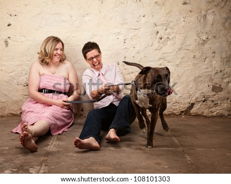 Laughing friends sitting on the floor with funny dog