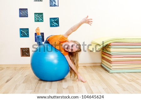 Laughing girl from a primary school lying on a large blue gymnastic ball - stock photo