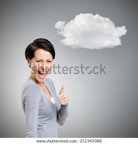 Laughing girl gives thumb up, isolated on grey background with cloud - stock photo