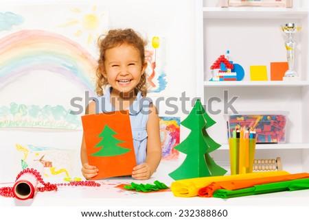 Laughing girl holding carton card with Xmas tree - stock photo