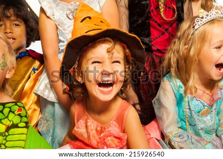 Laughing girl in Halloween costume with friends - stock photo