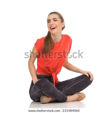 Laughing girl in red top, black jeans is sitting on the floor with legs crossed and looking away. Full length studio shot isolated on white. - stock photo