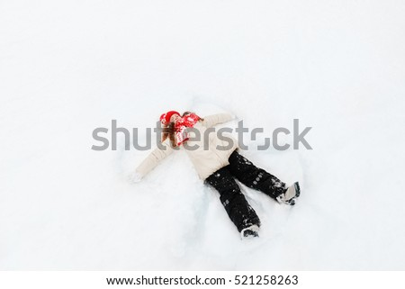Laughing girl laying on a snow moving her hand up and down, playing winter outdoors. Little girl on a snow showing angel figures.