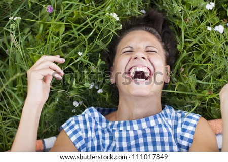 laughing girl lying on a lawn - rolling on the floor laughing