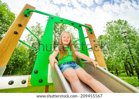 Laughing girl on children chute ready to slide