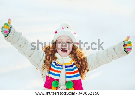 Laughing girl showing thumbs up in winter park. - stock photo