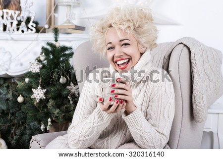 Laughing girl sitting in the chair. Happy smile, bright holiday emotions. Series of winter holiday photos. Christmas and New Year celebration - stock photo