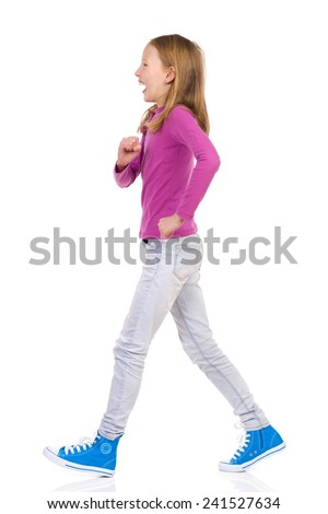 Laughing girl walking. Side view. Full length studio shot isolated on white.