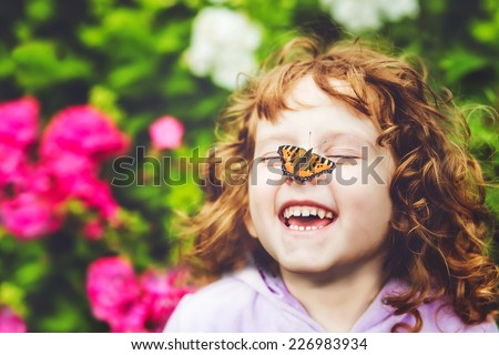 Laughing girl with a butterfly on his nose. - stock photo