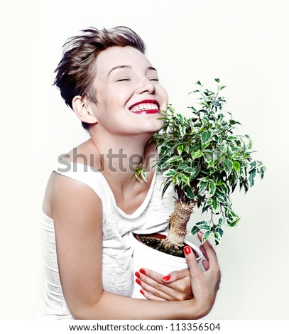 laughing girl with a plant in hand - stock photo