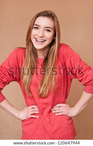 laughing girl with braces stroking a pose - stock photo