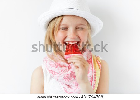 Laughing girl with red popsicle in white light room. Cheerful child eating her sugar candy with closed eyes. Delighted kid radiates positive emotions and summer holiday mood. - stock photo