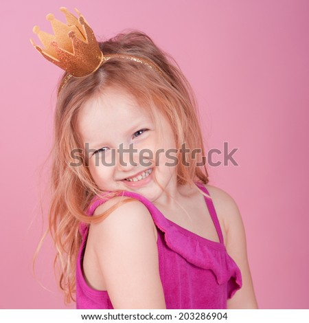 Laughing girl 3-5 years old wearing crown over pink
