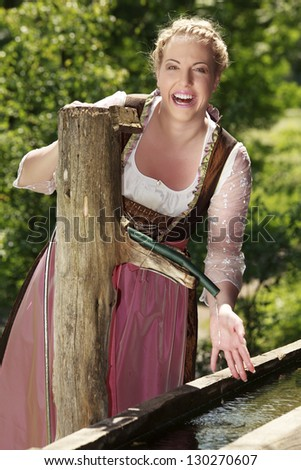 Laughing girls in Bavarian costume at a well / Laughing Bavarian girl