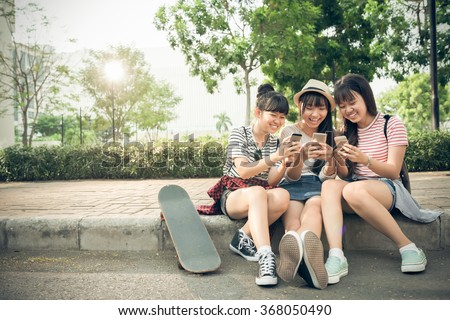 Laughing girls playing on their smartphones outdoors - stock photo