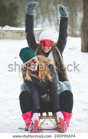 Laughing girls sledge downhill in wintertime enjoy snow - stock photo