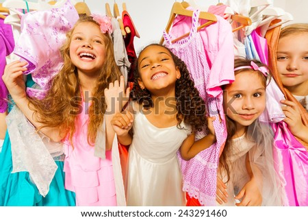 Laughing girls standing among colorful dresses - stock photo