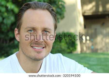 Laughing gorgeous guy with blond hair and blue eyes