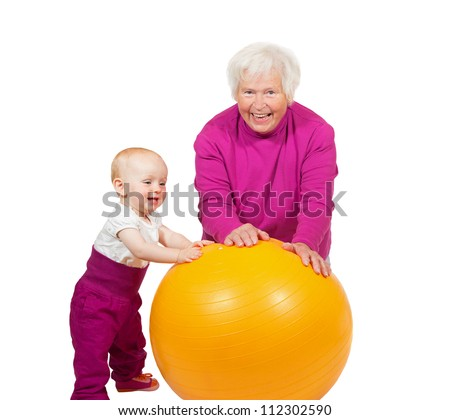 Laughing grandmother pausing in her exercises as her inquisitive little baby grandchild comes over to investigate the pilatses ball - stock photo