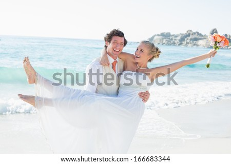 Laughing groom carrying his pretty blonde wife at the beach - stock photo