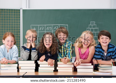 Laughing group of young school kids in class with young boys and girls leaning on piles of hard cover text books on a long table in front of a blackboard - stock photo