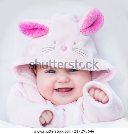 Laughing happy baby girl sitting in a white stroller in a bunny dress-up - stock photo