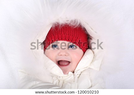 Laughing happy baby in a white snow suit and red knitted hat - stock photo