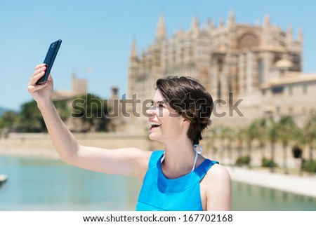 Laughing happy beautiful young woman taking her own portrait with her mobile phone in front of the cathedral on Mallorca - stock photo