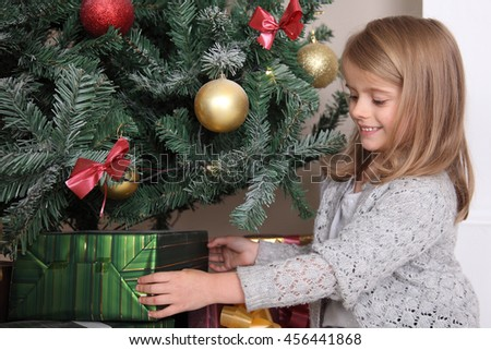 Laughing happy girl near Christmas tree with presents on the eve of the new year. - stock photo