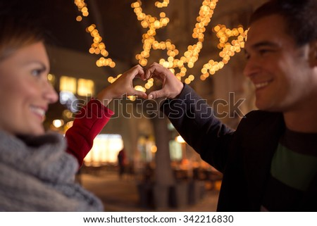 laughing happy lovers  making heart shape by their hands with Christmas light in background  - stock photo