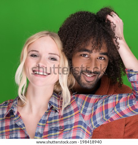 Laughing happy multiracial couple with a beautiful young blond female and handsome young African American male in a close loving embrace - stock photo