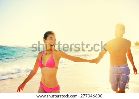Laughing happy romantic couple summer vacation beach fun. Joyful multi-ethnic young couple laughing elated together on tropical beach holiday on resort. Mixed race Asian woman and Caucasian man. - stock photo